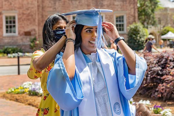 A student fixes another students graduation cap.